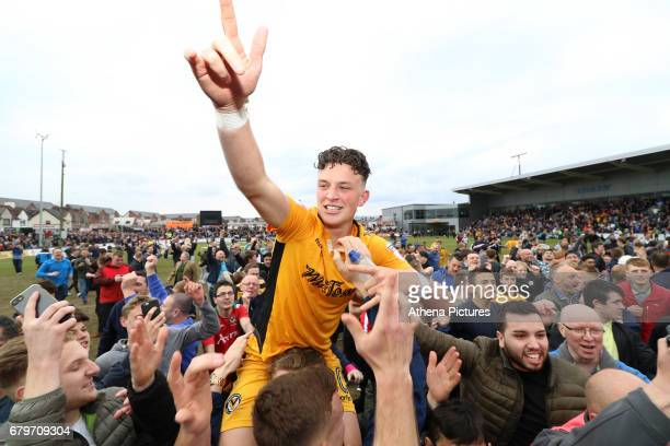 Tom OwenEvans of Newport County celebrates with fans during a pitch invasion after the final whistle as a late goal from Mark O'Brien secures safety...