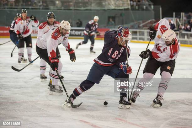 Tom Parisi of Team USA and Brett Ponich of Team Canada contest the puck during the Melbourne Game of the Ice Hockey Classic on June 24 2017 held at...