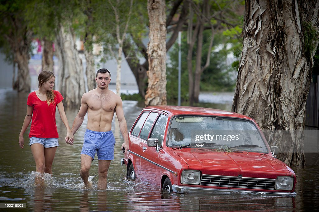 Tom Pfeffer (R) and his girlfriend Greta Devlin walk past a partly submerged car in the flooded inner Brisbane suburb of Newmarket on January 28, 2013 as high winds and heavy rains brought by ex-tropical cyclone Oswald have hit the state of Queensland. Helicopters plucked dozens of stranded Australians to safety in dramatic rooftop rescues on January 28 as severe floods swept the northeast, killing three people and inundating thousands of homes. AFP PHOTO / Patrick HAMILTON