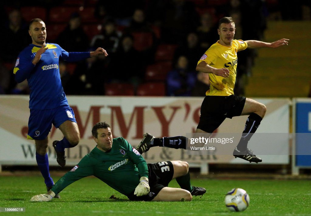 Tom Pope of Port Vale beats AFC Wimbledon keeper, <a gi-track='captionPersonalityLinkClicked' href=/galleries/search?phrase=Neil+Sullivan&family=editorial&specificpeople=624823 ng-click='$event.stopPropagation()'>Neil Sullivan</a> to score a goal during the npower League Two match between AFC Wimbledon and Port Vale at The Cherry Red Records Stadium on January 24, 2013 in Kingston upon Thames, England.