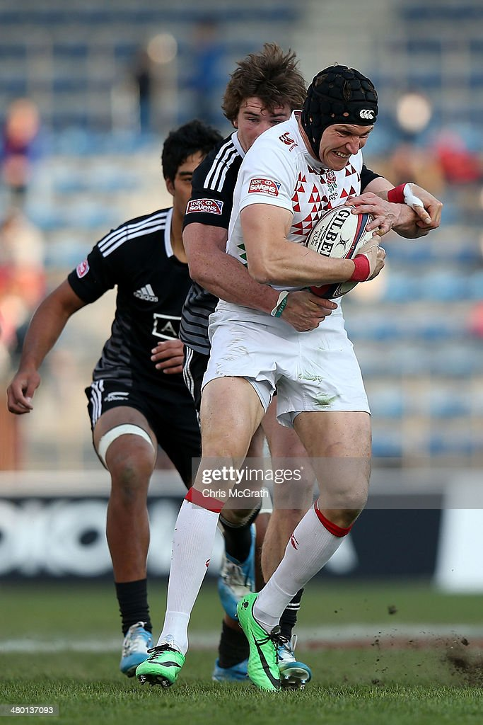 Tom Powell #8 of England is tackled by Sam Dickson #3 of New Zealand during the Tokyo Sevens, in the six round of the HSBC Sevens World Series at the Prince Chichibu Memorial Ground on March 23, 2014 in Tokyo, Japan.