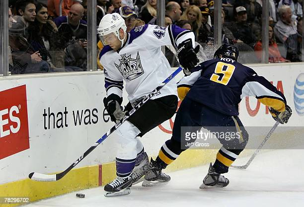 Tom Preissing of the Los Angeles Kings handles the puck under pressure from Derek Roy of the Buffalo Sabres during the first period of the NHL game...