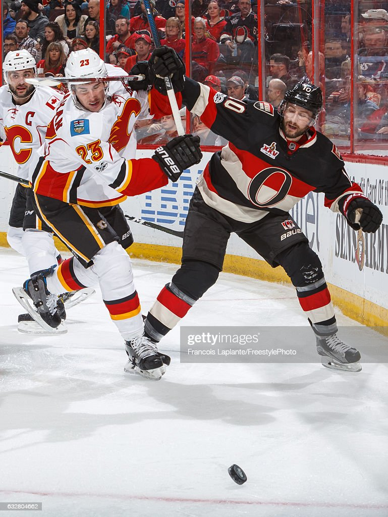 Tom Pyatt #10 of the Ottawa Senators battles for a loose puck against Sean Monahan #23 of the Calgary Flames during an NHL game at Canadian Tire Centre on January 26, 2017 in Ottawa, Ontario, Canada.