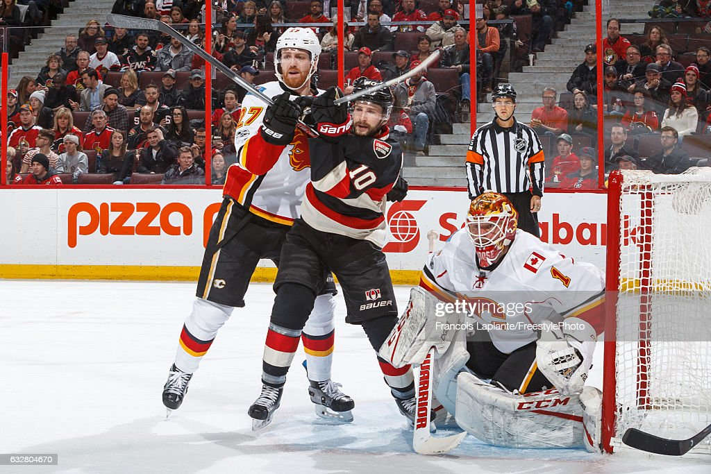 Tom Pyatt #10 of the Ottawa Senators battles for position against Dougie Hamilton #27 and goalie Brian Elliott #1 of the Calgary Flames during an NHL game at Canadian Tire Centre on January 26, 2017 in Ottawa, Ontario, Canada.