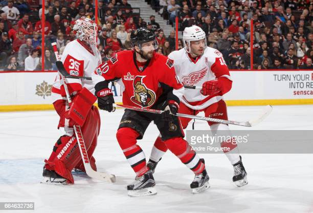 Tom Pyatt of the Ottawa Senators battles for position against Robbie Russo of the Detroit Red Wings in front of the net of Jimmy Howard at Canadian...