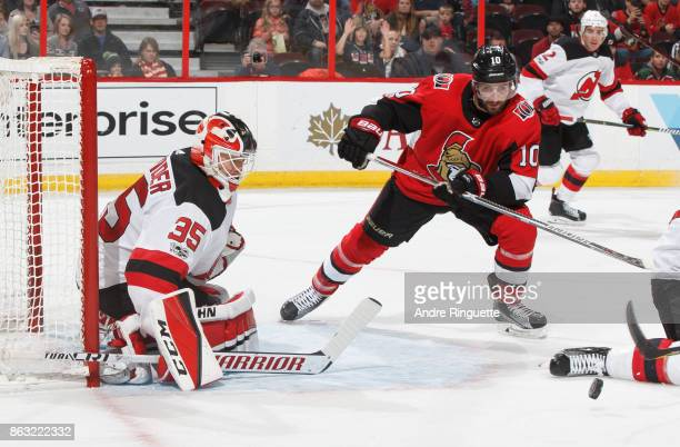 Tom Pyatt of the Ottawa Senators reaches for the rebound as Cory Schneider of the New Jersey Devils guards his net at Canadian Tire Centre on October...