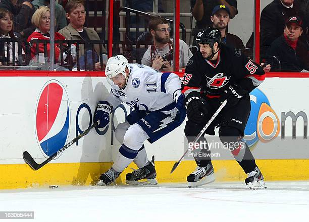 Tom Pyatt of the Tampa Bay Lightning battles along the boards for the puck with Chad LaRose of the Carolina Hurricanes during an NHL game on February...