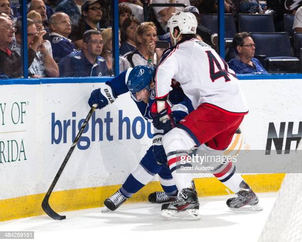 Tom Pyatt of the Tampa Bay Lightning battles for puck control against Jared Boll of the Columbus Blue Jackets during the third period at the Tampa...