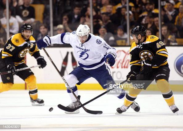 Tom Pyatt of the Tampa Bay Lightning battles for the puck against Rich Peverley of the Boston Bruins at TD Garden on March 27 2012 in Boston...