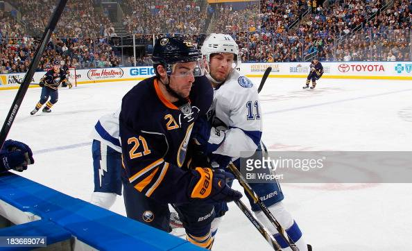 Tom Pyatt of the Tampa Bay Lightning checks Drew Stafford of the Buffalo Sabres into the boards on October 8 2013 at the First Niagara Center in...