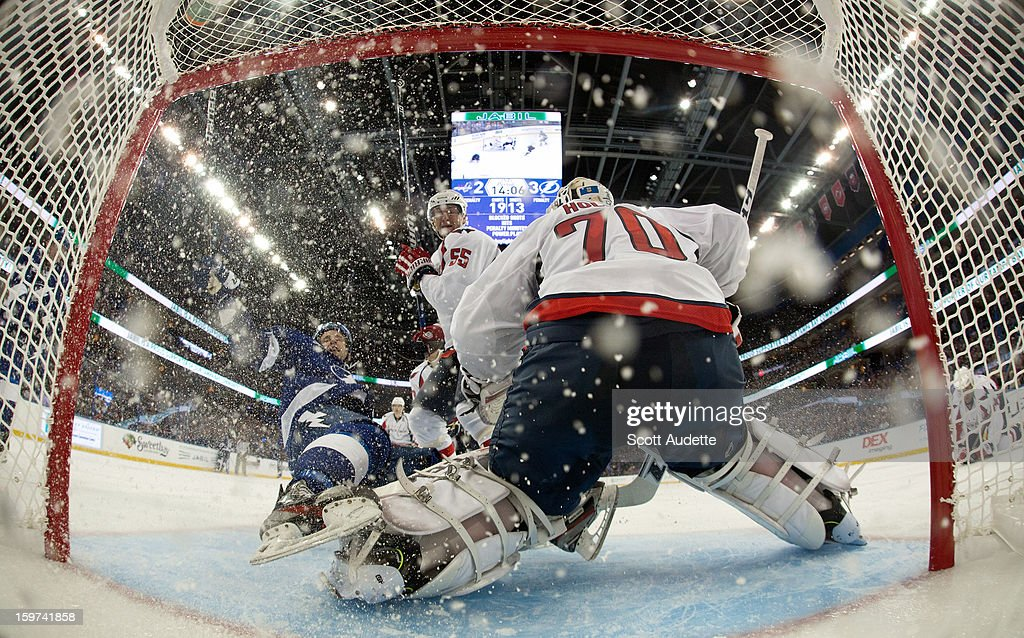 Tom Pyatt #11 of the Tampa Bay Lightning gets knocked down by Jeff Schultz #55 of the Washington Capitals in front of goaltender Braden Holtby #70 during the game at the Tampa Bay Times Forum on January 19, 2013 in Tampa, Florida.