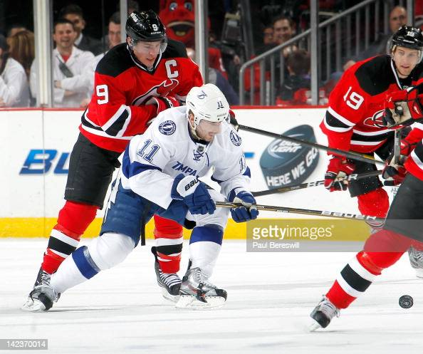 Tom Pyatt of the Tampa Bay Lightning is checked by Zach Parise of the New Jersey Devils during an NHL hockey game at Prudential Center on March 29...