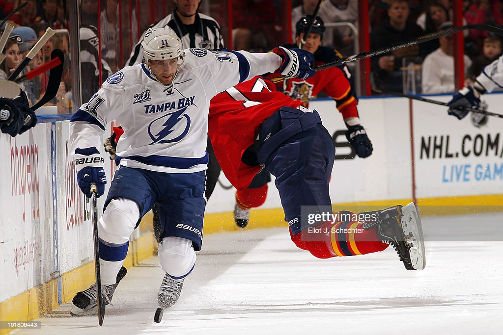 Tom Pyatt #11 of the Tampa Bay Lightning skates for possession against Tomas Fleischmann #14 of the Florida Panthers at the BB&T Center on February 16, 2013 in Sunrise, Florida.