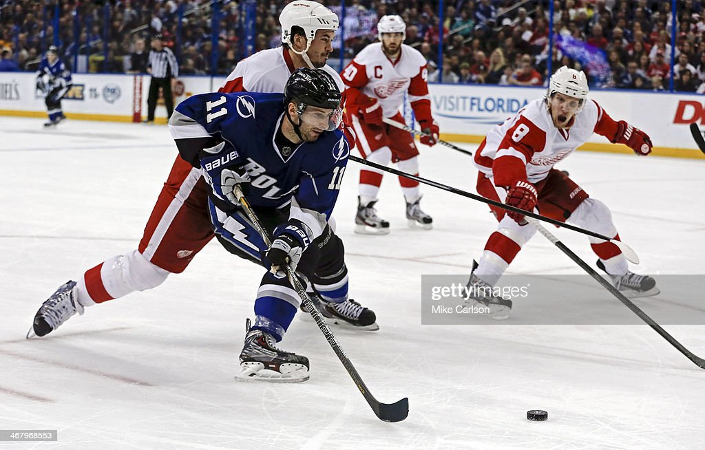 <a gi-track='captionPersonalityLinkClicked' href=/galleries/search?phrase=Tom+Pyatt&family=editorial&specificpeople=2079036 ng-click='$event.stopPropagation()'>Tom Pyatt</a> #11 of the Tampa Bay Lightning works his way past <a gi-track='captionPersonalityLinkClicked' href=/galleries/search?phrase=Jonathan+Ericsson&family=editorial&specificpeople=2538498 ng-click='$event.stopPropagation()'>Jonathan Ericsson</a> #52 and <a gi-track='captionPersonalityLinkClicked' href=/galleries/search?phrase=Justin+Abdelkader&family=editorial&specificpeople=2271858 ng-click='$event.stopPropagation()'>Justin Abdelkader</a> #8 of the Detroit Red Wings at the Tampa Bay Times Forum on February 8, 2014 in Tampa, Florida.