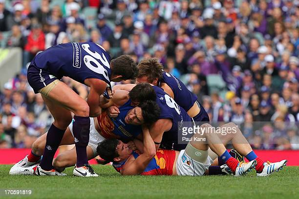 Tom Rockliff and Brent Staker of the Lions wrestle with Jack Hannath Nick Suban and Matt De Boer of the Dockers during the round 12 AFL match between...