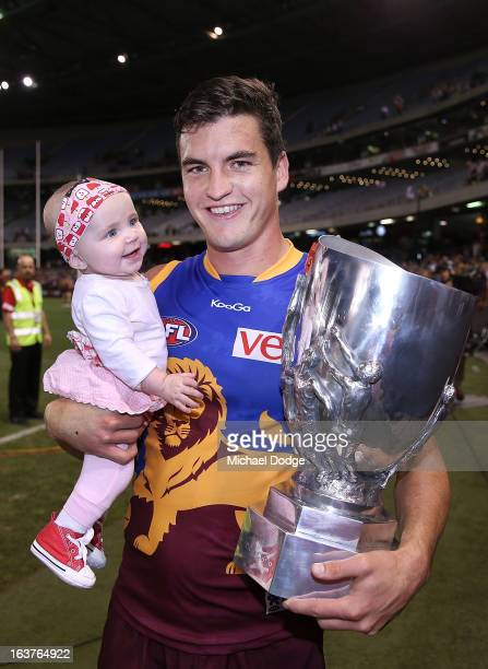 Tom Rockliff of the Brisbane Lions with his niece Meika and the trophy after their win in the NAB Cup AFL Grand Final match between the Carlton Blues...