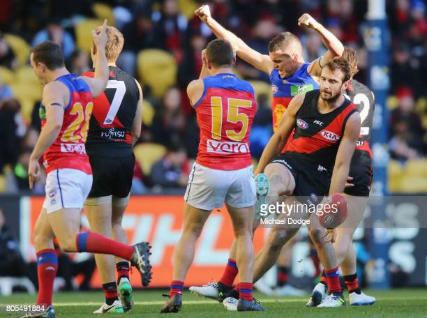Tom Rockliff of the Lions celebrates with Dayne Zorko and Lewis Taylor after their win on the final siren as Jobe Watson of the Bombers kicks the...