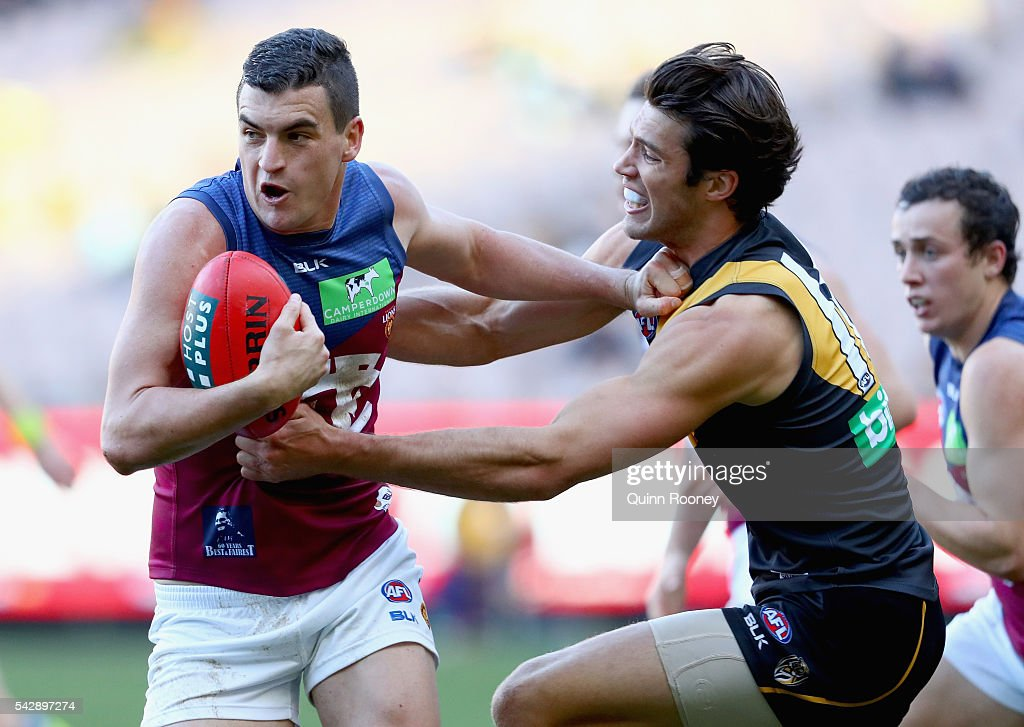 Tom Rockliff of the Lions fends off a tackle by Alex Rance of the Tigers during the round 14 AFL match between the Richmond Tigers and the Brisbane Lions at Melbourne Cricket Ground on June 25, 2016 in Melbourne, Australia.