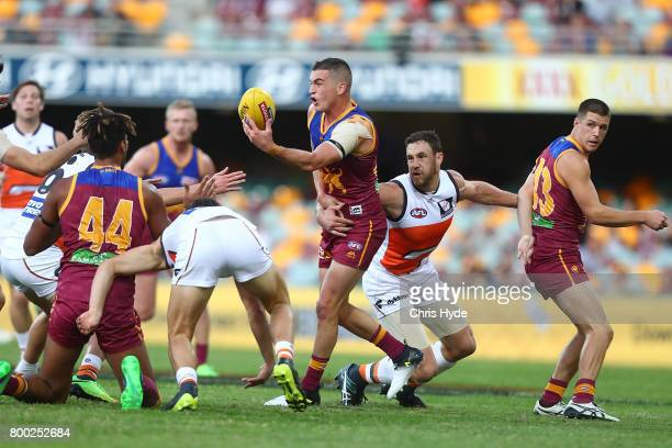 Tom Rockliff of the Lions handballs during the round 14 AFL match between the Brisbane Lions and the Greater Western Sydney Giants at The Gabba on...
