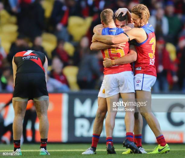 Tom Rockliff of the Lions is hugged by Dayne Zorko and Eric Hipwood after their winon the final siren during the round 15 AFL match between the...