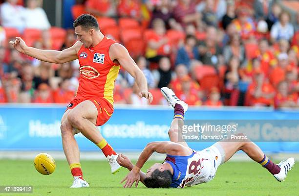 Tom Rockliff of the Lions is knocked out after colliding with Steven May of the Suns during the round five AFL match between the Gold Coast Suns and...