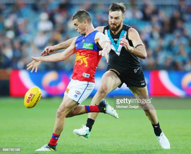 Tom Rockliff of the Lions kicks the ball away from Charlie Dixon of the Power during the round 13 AFL match between the Port Adelaide Power and the...