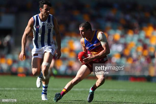 Tom Rockliff of the Lions runs the ball during the round 23 AFL match between the Brisbane Lions and the North Melbourne Kangaroos at The Gabba on...
