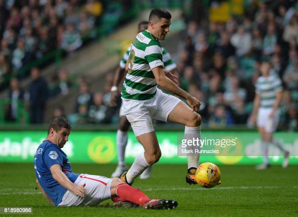 Tom Rogic of Celtic is challenged by Mark Haughey of Linfield during the UEFA Champions League Qualifying Second Round Second Leg match between...