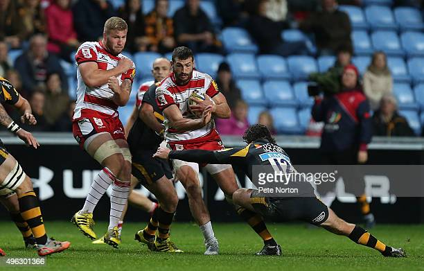 Tom Savage of Gloucester attempts to move forward with the ball past the challenge of Ben Jacobs of Wasps during the Aviva Premiership match between...