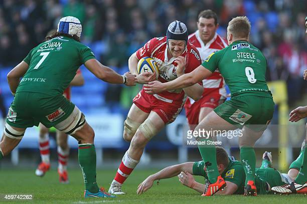 Tom Savage of Gloucester charges at Blair Cowan and Scott Steele of London Irish during the Aviva Premiership match between London Irish and...
