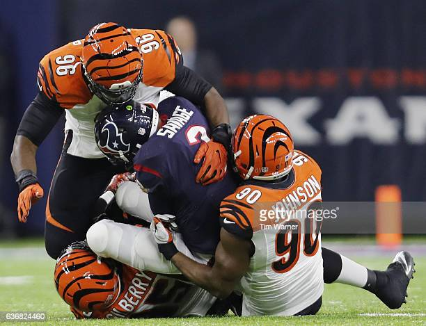 Tom Savage of the Houston Texans is tackled behind the line of scrimmage by Wallace Gilberry Michael Johnson and Carlos Dunlap of the Cincinnati...