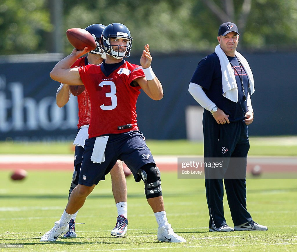 Tom Savage of the Houston Texans is watched by head coach Bill O'Brien as he works out during an NFL football organized team activity on June 1 2015...