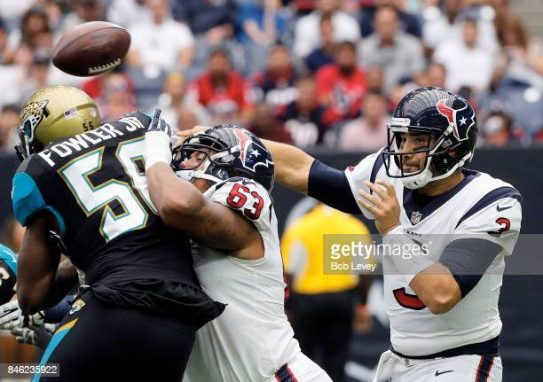 Tom Savage of the Houston Texans looks for a receiver as Kendall Lamm keeps Dante Fowler of the Jacksonville Jaguars away at NRG Stadium on September...