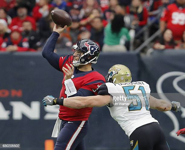 Tom Savage of the Houston Texans throws a pass under pressure by Paul Posluszny of the Jacksonville Jaguars in the second quarter at NRG Stadium on...