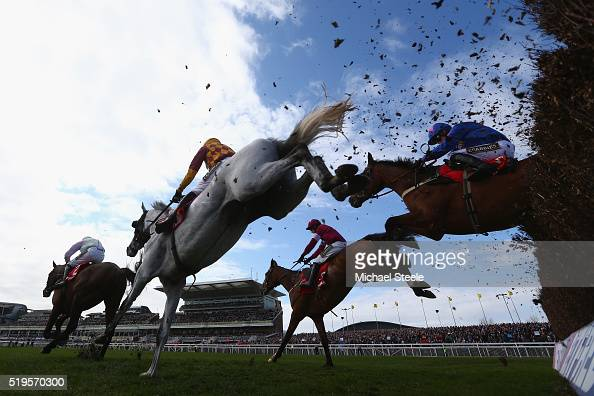 Tom Scudamore riding Dynaste clears a hurdle alongside eventual winner Paddy Brennan on Cue Card in the Betfred Bowl steeplechase at Aintree...