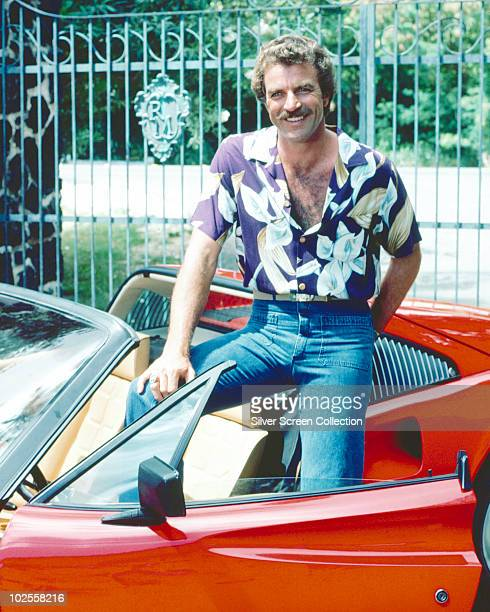 Tom Selleck as the titular investigator in the television series 'Magnum PI' circa 1985 He is posing with his red Ferrari 308
