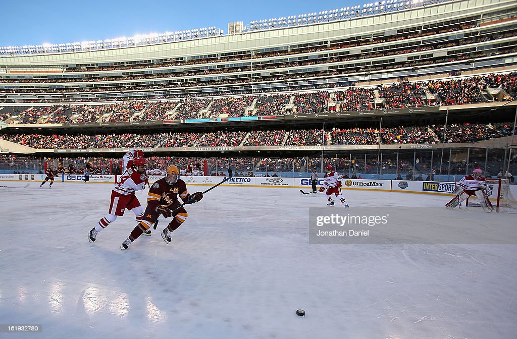 Tom Serratore #14 of the Minnesota Golden Gophers chases the puck with Jefferson Dahl #14 of the Wisconsin Badgers during the Hockey City Classic at Soldier Field on February 17, 2013 in Chicago, Illinois.