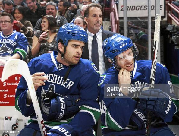 Tom Sestito Jannik Hansen and head coach John Tortorella of the Vancouver Canucks look on from the bench during the NHL game against the Florida...