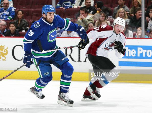 Tom Sestito of the Vancouver Canucks and Andre Benoit of the Colorado Avalanche skate up ice during their NHL game at Rogers Arena April 10 2014 in...