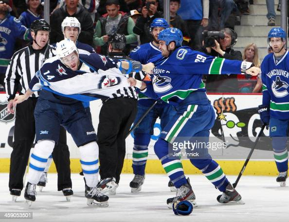 Tom Sestito of the Vancouver Canucks and Anthony Peluso of the Winnipeg Jets fight during their NHL game at Rogers Arena December 22 2013 in...