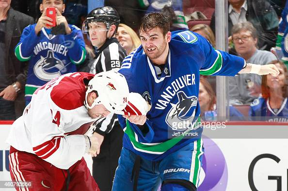 Tom Sestito of the Vancouver Canucks and Kyle Chipchura of the Arizona Coyotes fight during their NHL game at Rogers Arena December 22 2014 in...