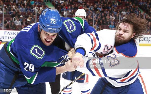 Tom Sestito of the Vancouver Canucks and Luke Gazdic of the Edmonton Oilers fight during their game at Rogers Arena on October 5 2013 in Vancouver...