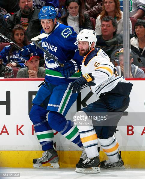 Tom Sestito of the Vancouver Canucks and Mike Weber of the Buffalo Sabres skate after a loose puck during their NHL game at Rogers Arena March 23...