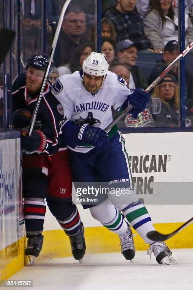 Tom Sestito of the Vancouver Canucks checks James Wisniewski of the Columbus Blue Jackets into the boards during the second period on October 20 2013...