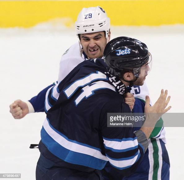 Tom Sestito of the Vancouver Canucks fights with Anthony Peluso of the Winnipeg Jets during first period action in an NHL game at the MTS Centre on...