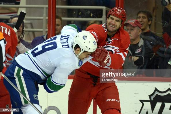 Tom Sestito of the Vancouver Canucks fights with Jay Harrison of the Carolina Hurricanes at PNC Arena on December 1 2013 in Raleigh North Carolina