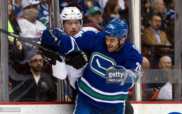 Tom Sestito of the Vancouver Canucks hits Erik Johnson of the Colorado Avalanche along the end boards during the second period in NHL action on April...