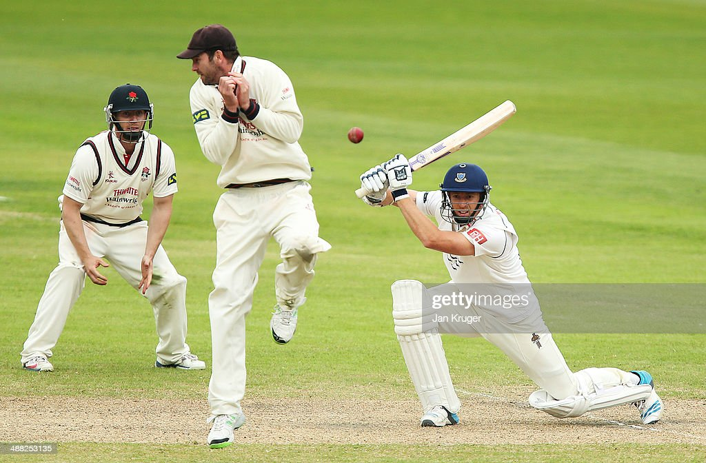 Tom Smith of Lancashire (C) evades the cover drive of James Anyon of Sussex during the LV County Championship match between Lancashire and Sussex at Old Trafford on May 4, 2014 in Manchester, England.
