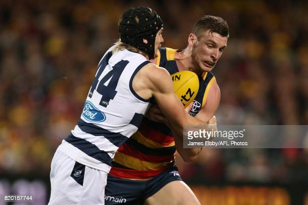 Tom Stewart of the Cats tackles Josh Jenkins of the Crows during the 2017 AFL round 18 match between the Adelaide Crows and the Geelong Cats at the...