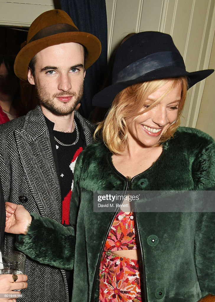 Tom Sturridge (L) and Sienna Miller attend the LOVE Christmas party at George on December 18, 2015 in London, England.